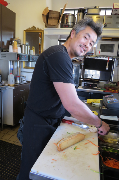 Photo by Marty Cheek Jonty's owner John Nguyen prepares a sandwich in his shop near the train station.