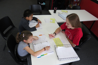Photo by Marty Cheek From left, Brianna Bouton, 7, Mekhi David, 8, get math help from Learning Center Instructor Ariel Masbrucker.