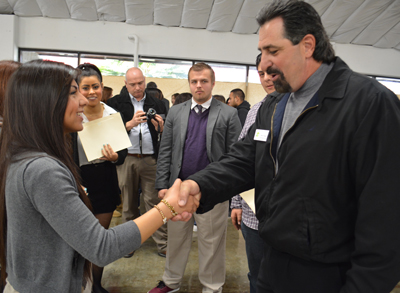 Photo by Marlene Guerrero Crystell Rodriguez, a 17-year-old Central High School junior, learns how to properly shake hands from Morgan Hill Chamber of Commerce Chairman Rich Firato during the recent Rock the Mock .