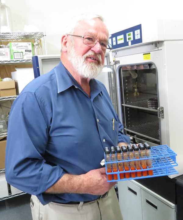 Anaerobe Systems owner Mike Cox displays test tubes growing microbes in his Morgan Hill lab. Photo by Marty Cheek