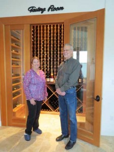 Photo by Marty Cheek The Ditmores in front of their fine wine collection in their Morgan Hill home.