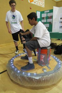 Satyen Patel,  an eighth-grade student at Britton Middle School, is coached by Corey Baldyga, an Oakwood School ninth grader, on maneuvering his home-built hovercraft. Photo by Marty Cheek