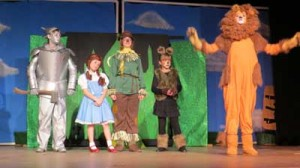 "Elijah Knight as ""Tin Man,""' Alyssa Webb as ""Dorothy Gale,"" Skylla Larson as ""Scarecrow,"" and Maya King as ""Toto"" listen to Ellen Menke as ""Cowardly Lion"" sing about being the ""King of the Forest."""