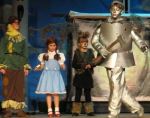The Tin Man dances after being oiled and regaining movement as the Scarecrow, Dorothy and Toto watch on.