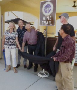 From left, Gilroy Visitors Bureau Executive Director Jane Howard, Santa Clara County Supervisor Mike Wasserman, President of the Santa Clara Valley Wine Grower's Association Mike Sampognaro, Morgan Hill Mayor Steve Tate, and local dentist Jon Hatakeyama unveil the Wine Trail sign at the one-year celebration at Lion Ranch Winery.