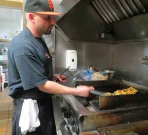 Jimmy Khoury, prep chef, prepares a kebab for Mr. Falafel customers at the downtown eatery. Photo by Marty Cheek