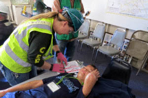 "Photo by Marty Cheek Morgan Hill CERT student Kristyn Bell Morin inspects a volunteer ""victim"" for injuries in a simulation of an earthquake emergency."
